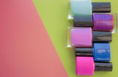Bottiglie dello smalto di chiodo Un gruppo di manicuri luminosi su un rosa, fondo verde Con spazio vuoto a sinistra fotografia stock libera da diritti