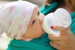 Bottiglie di acqua della bevanda della figlia di elasticità della madre Fotografia Stock