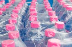 Bottiglie di acqua in involucro di plastica Fotografie Stock