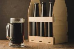 bottiglie di birra caso e bottiglie caso e tazza di /beer della tazza su una tavola di legno Fuoco selettivo immagini stock