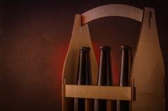 bottiglie di birra in una scatola di legno su un fondo di luce rossa/bottiglie di birra in una scatola di legno su un fondo di lu fotografia stock libera da diritti