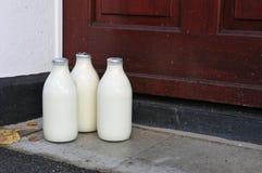 Bottiglie di latte su un gradino della porta Immagine Stock Libera da Diritti