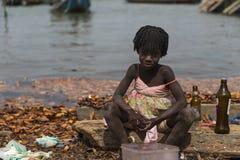 Bottiglie di lavaggio della ragazza accanto all'acqua nel porto della città di Cacheu, in Guinea-Bissau Fotografia Stock Libera da Diritti