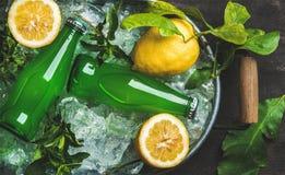 Bottiglie di limonata verde su ghiaccio scheggiato in vassoio del metallo fotografia stock