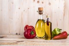Bottiglie di olio d'oliva con le paprica su struttura di legno leggera fotografia stock