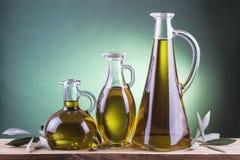Bottiglie di olio d'oliva su un fondo verde del riflettore Fotografie Stock