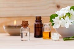 Bottiglie di olio dell'aroma sistemate con i fiori del gelsomino Fotografie Stock Libere da Diritti