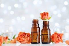 Bottiglie di olio essenziale di Rosa sulla tavola bianca con effetto del bokeh Stazione termale, aromaterapia, benessere, fondo d fotografia stock libera da diritti