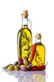 Bottiglie di Olive Oil con pepe e le erbe su bianco Immagine Stock