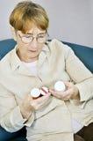 Bottiglie di pillola anziane della lettura della donna Fotografia Stock Libera da Diritti