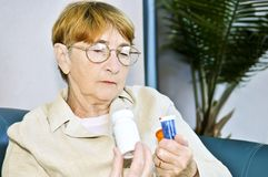 Bottiglie di pillola anziane della lettura della donna Fotografie Stock Libere da Diritti