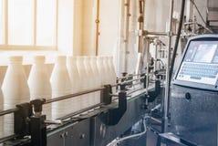 Bottiglie di plastica bianche con il prodotto lattiero-caseario sulla linea di produzione In bottiglia sul trasportatore fotografie stock libere da diritti