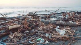 Bottiglie di plastica ed altra immondizia scaricate sulla spiaggia nera Inquinamento ambientale stock footage