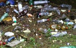 Bottiglie di plastica ed altri rifiuti sul fiume inquinante Fotografia Stock
