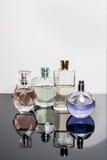 Bottiglie di profumo differenti con le riflessioni Profumeria, cosmetici Fotografia Stock
