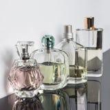Bottiglie di profumo differenti con le riflessioni Profumeria, cosmetici Fotografie Stock