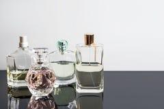Bottiglie di profumo differenti con le riflessioni Profumeria, cosmetici Spazio libero per testo Fotografie Stock
