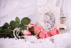 Bottiglie di profumo, rose dentellare e blocco per grafici Fotografia Stock