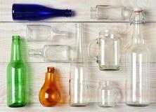 Bottiglie di vetro assortite su legno bianco Fotografia Stock