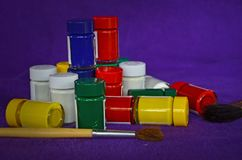 Bottiglie di vetro dei colori di manifesto sui vestiti viola Fotografie Stock