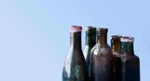 Bottiglie di vetro di progettazione antica su fondo blu Insieme sporco invecchiato variopinto del flacon copi lo spazio, foto ori Immagine Stock Libera da Diritti