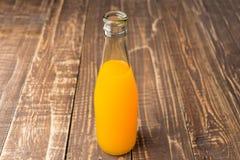 Bottiglie di vetro di succo d'arancia sul fondo di legno della tavola Fotografia Stock