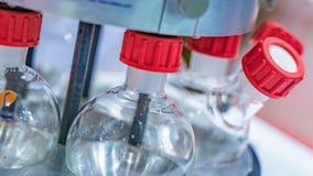 Bottiglie di vetro di esperimento con il dispositivo di scienza immagine stock