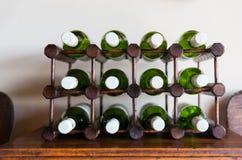 Bottiglie di vino bianco immagazzinate sullo scaffale di legno Immagini Stock