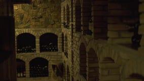 Bottiglie di vino che si trovano nella pila alla cantina in locanda Bottiglie di vetro di vino immagazzinate in cantina di pietra stock footage