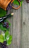 Bottiglie di vino con l'uva, canestro, due bicchieri di vino su legno rustico Fabbricazione di vino verticale Fotografie Stock Libere da Diritti