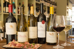 Bottiglie di vino con le etichette vaghe, i bicchieri di vino e un piatto della ghiottoneria Fotografia Stock Libera da Diritti