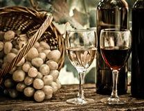 Bottiglie di vino, due vetri ed uva in cestino Immagini Stock
