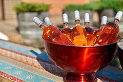 Bottiglie di vino rosato in un secchio di ghiaccio sulla tavola Immagini Stock Libere da Diritti