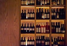 Bottiglie di vino su uno scaffale di legno Immagini Stock