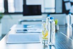 bottiglie e vetri con la bevanda antiossidante per la riunione d'affari nell'ufficio fotografia stock libera da diritti