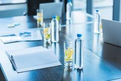bottiglie e vetri con la bevanda antiossidante per la riunione d'affari sulla tavola fotografia stock