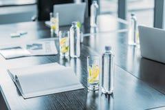 bottiglie e vetri con la bevanda antiossidante per la riunione d'affari sulla tavola immagini stock
