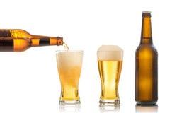 Bottiglie e vetri di birra su fondo bianco Fotografia Stock