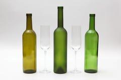 Bottiglie e vetri di vino vuoti su un fondo bianco Fotografie Stock