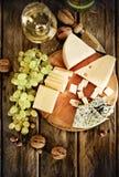 Bottiglie e vetro di vino bianco, di formaggio, dei dadi e dell'uva Immagine Stock
