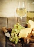 Bottiglie e vetro di vino bianco, di formaggio, dei dadi e dell'uva Immagini Stock
