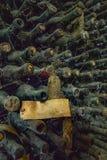 Bottiglie molto vecchie e polverose impilate in magazzino fotografie stock