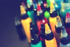 Bottiglie multiple con gli inchiostri variopinti per il tatuaggio, fine su immagini stock