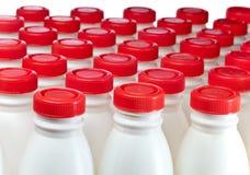 Bottiglie per il latte. Ancora-vita su una priorità bassa bianca Fotografie Stock