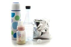 Bottiglie per il latte del bambino, bottiglie di acqua, bottiglia di acqua calda e cucchiaio per Fotografia Stock