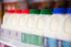 Bottiglie per il latte riordinate in scaffale Immagini Stock Libere da Diritti