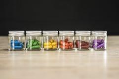 Bottiglie riempite di pillole colorate di prescrizione allineate Fotografie Stock Libere da Diritti