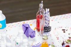Bottiglie sulla tavola sudicia dopo la festa di compleanno immagine stock libera da diritti