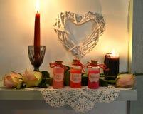 Bottiglie sveglie con felicità, la pozione di amore, l'elisir magico e le rose nel lume di candela immagine stock
