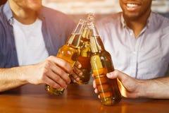 Bottiglie tintinnanti di birra Uomini che hanno resto in pub immagine stock libera da diritti